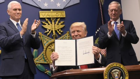 US President Donald Trump holds up an executive action on rebuilding the armed forces after signing it on January 27, 2017 at the Pentagon in Washington, DC. Looking on are US Vice President Mike Pence (L) and US Defense Secretary James Mattis. / AFP / MANDEL NGAN        (Photo credit should read MANDEL NGAN/AFP/Getty Images)
