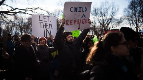 A man carries a sign supporting refugees prior to marching from Battery Park to Foley Square in the Manhattan borough of New York, NY on Saturday, January 29, 2017.