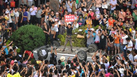 A man holds a placard as he stands on a car overturned by a group of anti-pollution protestors on July 28, 2012.