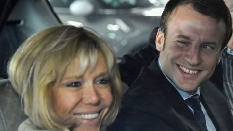 Former French Economy Minister Emmanuel Macron (R) smiles next to his wife Brigitte Macron as they arrive at the station of Le Mans prior to a political meeting on October 11, 2016. / AFP / JEAN-FRANCOIS MONIER        (Photo credit should read JEAN-FRANCOIS MONIER/AFP/Getty Images)
