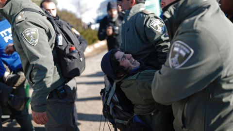 Israeli security forces carry an Israeli settler on the second day of an operation to evict occupants from the West Bank outpost of Amona on February 2, 2017.