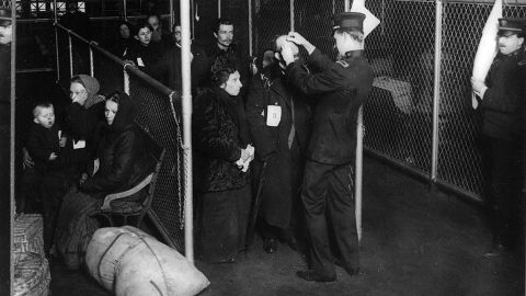 US inspectors examine the eyes of immigrants at Ellis Island in New York Harbor, in the early 1900s.