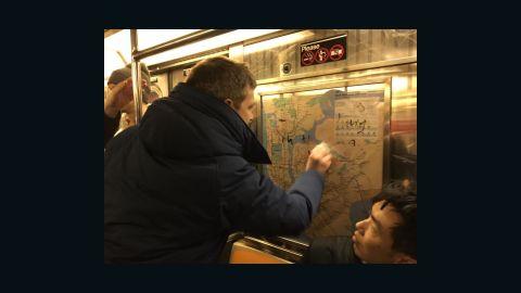 Chef Jared Nied scrubs graffiti from the subway car Saturday night.