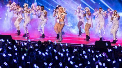 Audience members wave lights.