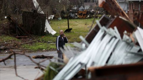 A man looks at the destruction as he talks on the phone.