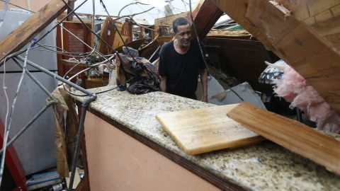 Gregory Rugon looks for his glasses at the spot where he took cover in his home.