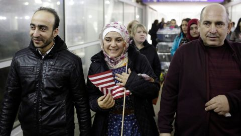 Syrian refugee Baraa Haj Khalaf holds the American flag as she walks with her husband Abdulmajeed and father Khaled Haj Khalaf as she leaves O'Hare International Airport on February 7, 2017 in Chicago, Illinois.