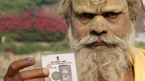 An Indian sadhu - holy man - displays his inked finger and voter card after casting vote in Ayodhya on May 7,2014. More than 95 million voters are eligible to vote in 64 seats in the penultimate leg of the world's biggest general election that ends with results on May 16.  AFP PHOTO        (Photo credit should read STR/AFP/Getty Images)