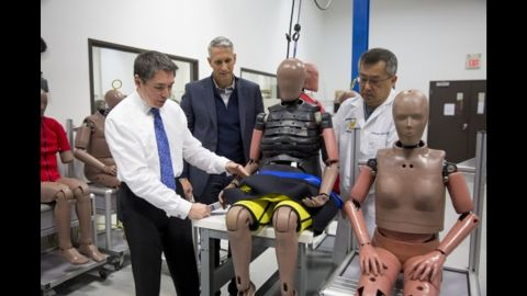 """Dr. Stewart Wang demonstrates how to secure an """"elderly"""" crash-test dummy."""