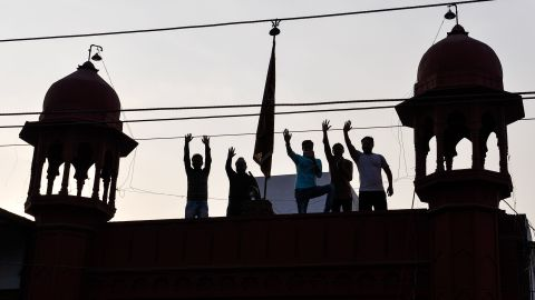 Supporters wave from a rooftop as they attend a joint election campaign rally by Chief Minister, Akhilesh Yadav, and Congress party vice president, Rahul Gandhi, in February 2017.
