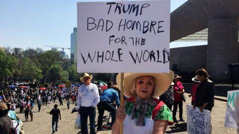"""Maria Eugenia Montes de Oca holds up a sign lambasting Trump as a """"bad hombre."""""""