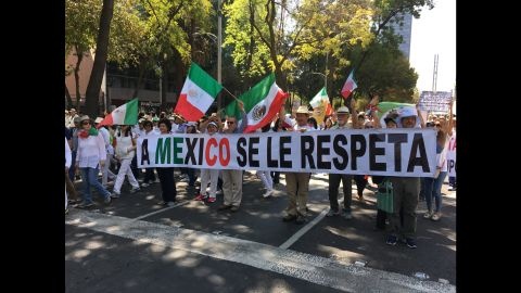 """Protesters in Mexico City march behind a banner that says """"You respect Mexico."""""""