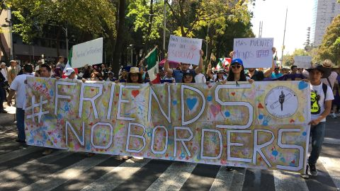 """Protesters hold a banner that reads """"#Friends, No Borders."""" Additional signs from left to right: """"#friendship with no borders,"""" """"to govern you have to listen,"""" """"Less walls."""""""