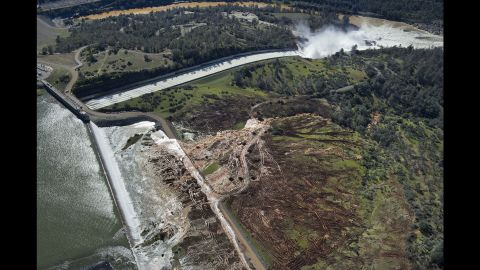Water flows over an emergency spillway (bottom right) at Lake Oroville Dam on Saturday, February 11. The damage has affected both the primary and the emergency spillways, which serve as channels to drain water from the lake to prevent overflow.