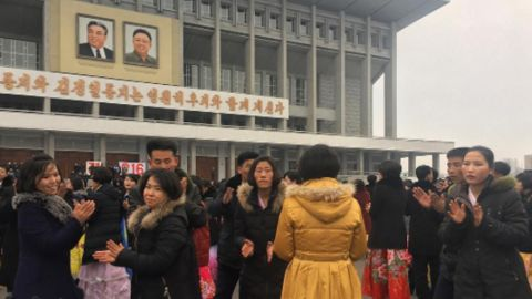 University students dance in front of the Pyongyang indoor stadium on February 16.