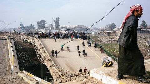 Mosul residents cross a damaged bridge in the al-Sukkar neighborhood on Saturday, January 21.