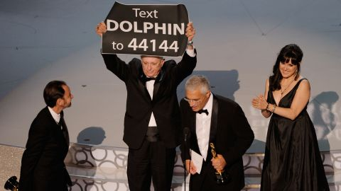 """When Louie Psihoyos and Fisher Stevens won the best documentary feature award for """"The Cove"""" at the 82nd Academy Awards on March 7, 2010, they were accompanied on stage by producer Paula DuPré Pesmen and film subject Ric O'Barry. O'Barry walked on stage carrying a sign that prompted the audience to text for more information on how to help curtail the dolphin slaughter depicted in the film."""