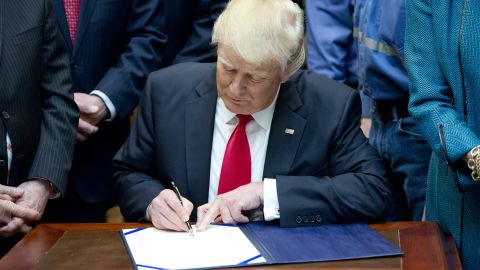 """WASHINGTON, DC - FEBRUARY 16:  U.S. President Donald Trump signs H.J. Res. 38, disapproving the rule submitted by the US Department of the Interior known as the Stream Protection Rule in the Roosevelt Room of the White House on February 16, 2017 in Washington, DC.  The Department of Interior's Stream Protection Rule, which was signed during the final month of the Obama administration, """"addresses the impacts of surface coal mining operations on surface water, groundwater, and the productivity of mining operation sites,"""" according to the Congress.gov summary of the resolution. (Photo by Ron Sachs-Pool/Getty Images)"""