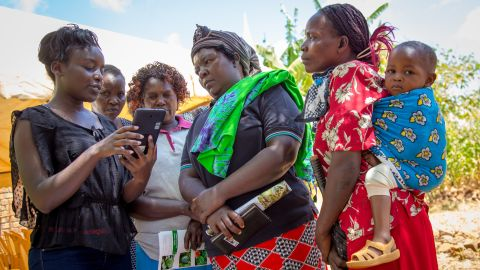 Female farmers learn to use the Mbegu Choice app in Kenya.