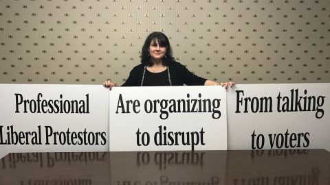 Candace Preston, a staffer for Rep. Gaetz, holds up signs that are his backup plan if protestors disrupt his Thursday night town hall - his speech printed entirely on posters.