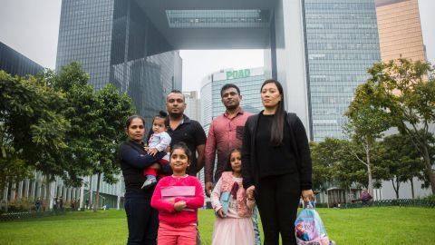 Sri Lankan refugee Supun Thilina Kellapatha (third from left), his partner Nadeeka (left), with their baby boy Dinath, daughter Sethumdi, Sri Lankan refugee Ajith Puspa (third from right) and Filipino refugee Vanessa Rodel (right) with her daughter Keana pose for a photo in front of the government buildings of Hong Kong in 2017.