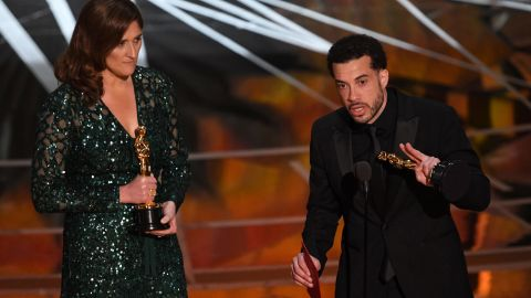 """Director Ezra Edelman delivers a speech next to producer Caroline Waterlow after """"O.J.: Made In America"""" won the Oscar for best documentary feature. """"O.J.: Made In America"""" was a five-part miniseries that explored the life of former football star O.J. Simpson."""