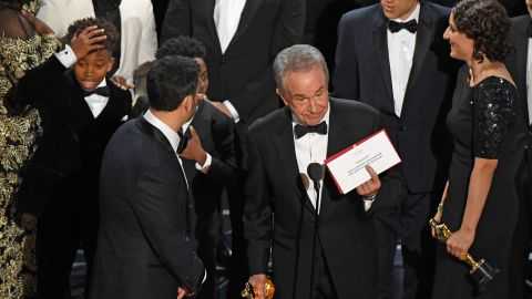 """The cast of """"Moonlight"""" and """"La La Land"""" appear on stage as presenter Warren Beatty shows the winner's envelope for Best Movie """"Moonlight"""" on stage."""