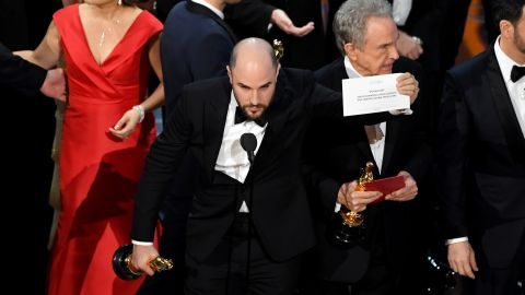 """""""La La Land"""" producer Jordan Horowitz holds up the winner card to the audience, proving that """"Moonlight"""" had indeed won. Presenter Warren Beatty, seen behind Horowitz, told the crowd that he was given the wrong envelope."""