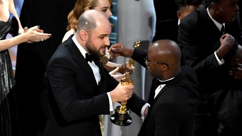 """''La La Land"""" producer Jordan Horowitz hands over the Best Picture award to """"Moonlight"""" writer/director Barry Jenkins following a presentation error onstage during the 89th Annual Academy Awards. (Photo by Kevin Winter/Getty Images)"""