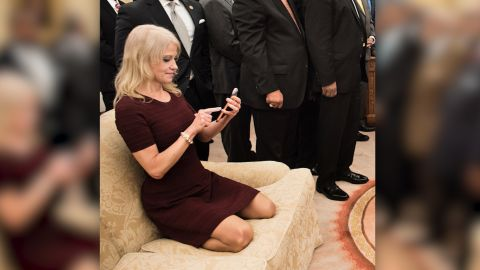 TOPSHOT - Counselor to the President Kellyanne Conway (L) checks her phone after taking a photo as US President Donald Trump and leaders of historically black universities and colleges pose for a group photo in the Oval Office of the White House before a meeting with US Vice President Mike Pence February 27, 2017 in Washington, DC. / AFP / Brendan Smialowski        (Photo credit should read BRENDAN SMIALOWSKI/AFP/Getty Images)
