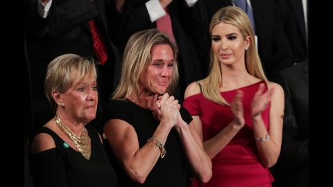 """Carryn Owens, center, cries as she is applauded by the chamber during Trump's speech. Owens' husband, Navy SEAL William """"Ryan"""" Owens, recently was killed during a mission in Yemen. """"Ryan died as he lived: a warrior and a hero, battling against terrorism and securing our nation,"""" Trump said. The applause lasted over a minute, which Trump said must be a record."""