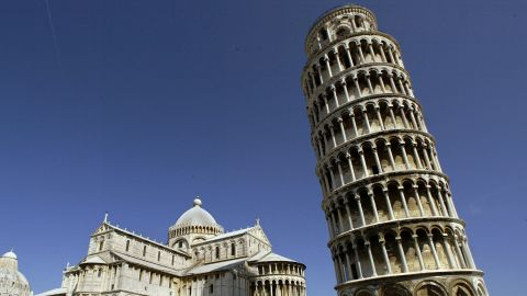 """PISA, ITALY - AUGUST 24:  Tourists visit the Leaning Tower of Pisa and the Cathedral in the """"Square of Miracle"""" August 24, 2002 in Pisa, Italy. The tower reopened in December 2001 after 10 years of stabilization work.  Visitors can, through the end of August, go to the top of the tower during the night.  (Photo by Franco Origlia/Getty Images)"""