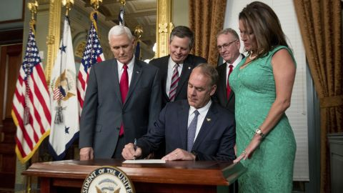"""New Interior Secretary Ryan Zinke signs an official document after he was <a href=""""http://www.cnn.com/2017/03/01/politics/ryan-zinke-confirmation-vote-interior-secretary/"""" target=""""_blank"""">confirmed by the Senate</a> on Wednesday, March 1. The former congressman from Montana was joined by his wife, Lolita, as well as Vice President Mike Pence, US Sen. Steve Daines and Montana Attorney General Tim Fox."""