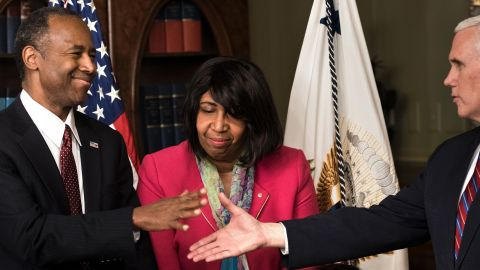 US Secretary of Housing and Urban Development Ben Carson (L) is congratulated by US Vice President Mike Pence (R) as his wife Candy Carson (2L) and granddaughter Tesora Carson watch during his swearing in ceremony in the Eisenhower Executive Office Building on March 2, 2017 in Washington, DC. / AFP PHOTO / Brendan Smialowski        (Photo credit should read BRENDAN SMIALOWSKI/AFP/Getty Images)