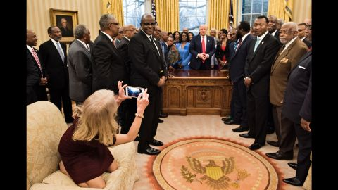"""White House Adviser Kellyanne Conway takes an Oval Office photo of President Trump and leaders of historically black colleges and universities on Monday, February 27. The image of her kneeling on the couch <a href=""""http://www.cnn.com/videos/politics/2017/02/28/kellyanne-conway-oval-couch-photo-orig-vstan.cnn"""" target=""""_blank"""">sparked memes on social media.</a>"""