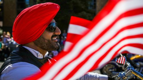 """A Sikh man rides on a motorcycle with the """"Sikh Riders of America"""" group during the 4th of July Parade in Alameda, California on Monday, July 4, 2016. / AFP / GABRIELLE LURIE        (Photo credit should read GABRIELLE LURIE/AFP/Getty Images)"""