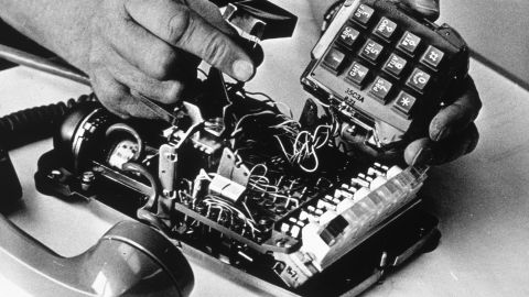 circa 1968:  A man placing a tap in a phone.  (Photo by MPI/Getty Images)