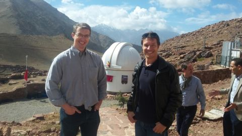 Gillon and Jehin pose with one of their telescopes.