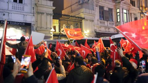Supporters of Turkey's President Recep Tayyip Erdogan wave flags outside the Dutch consulate during a protest, in Istanbul, early Sunday, March 12, 2017.