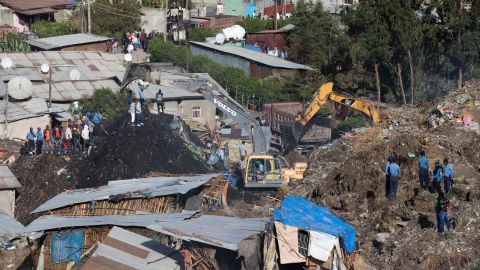 Excavators move mounds of trash Sunday as rescuers look for any possible survivors after the landslide.