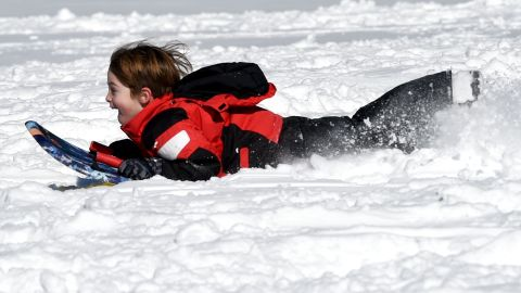 """A child goes sledding down a hill in Bruce Park in Greenwich, Connecticut on January 24, 2016. Millions of people in the eastern United States started digging out Sunday from a huge blizzard that brought New York and Washington to a standstill, but the travel woes were far from over. The storm -- dubbed """"Snowzilla"""" -- killed at least 18 people after it walloped several states over 36 hours on Friday and Saturday, affecting an estimated 85 million residents who were told to stay off the roads and hunker down in doors for their own safety. / AFP / Timothy A. CLARY        (Photo credit should read TIMOTHY A. CLARY/AFP/Getty Images)"""