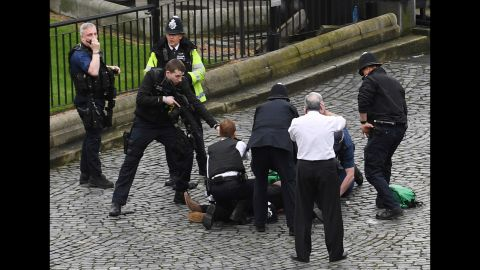 """An armed police officer stands over the attacker, identified as Khalid Masood, outside Parliament. """"It appeared that a car was coming towards the House of Commons mowing down pedestrians on the way,"""" Member of Parliament Gerald Howarth told CNN. """"The driver then got access to the parliamentary estate, stabbed a police officer and was shot."""""""