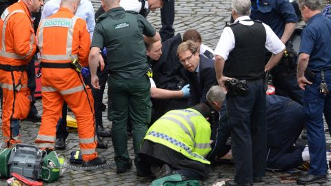 """Member of Parliament Tobias Ellwood, in the glasses, <a href=""""http://edition.cnn.com/2017/03/22/world/tobias-ellwood-london-rescue/index.html"""" target=""""_blank"""">tends to one of the injured people</a> amid the chaos. The man the politician was trying to save was a police officer who died, a witness on the scene told CNN. Authorities identified the deceased officer as Keith Palmer, 48."""