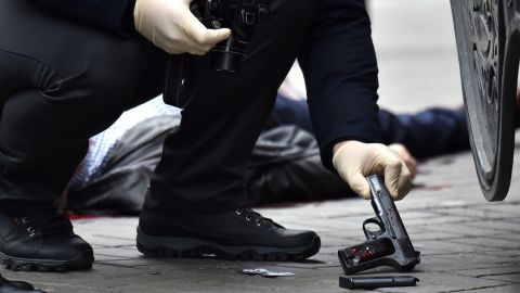 """EDITORS NOTE: Graphic content / An Ukrainian police expert seizes a gun at the scene where former Russian MP Denis Voronenkov was shot dead on March 23, 2017 in the center of Kiev.Ukrainian President blamed Russia for the murder of Voronenkov, who moved to Ukraine last year and was wanted by Russia for fraud, saying it was an """"act of state terrorism.""""  / AFP PHOTO / Sergei SUPINSKY        (Photo credit should read SERGEI SUPINSKY/AFP/Getty Images)"""