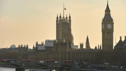 A picture shows red London buses, pedestrians and traffic crossing Westminster Bridge over the River Thames with the Union flag atop the Houses of Parliament (R) flying at half-mast in central London on March 23, 2017.  Britain's parliament reopened on Thursday with a minute's silence in a gesture of defiance a day after an attacker sowed terror in the heart of Westminster, killing three people before being shot dead. Sombre-looking lawmakers in a packed House of Commons chamber bowed their heads and police officers also marked the silence standing outside the headquarters of London's Metropolitan Police nearby.  / AFP PHOTO / Niklas HALLE'N        (Photo credit should read NIKLAS HALLE'N/AFP/Getty Images)