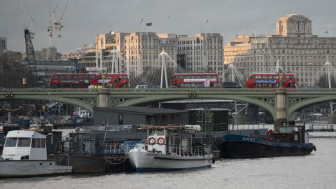 Police and forensics officers investigate near buses abandoned on Westminster Bridge following a terror attack on March 22.