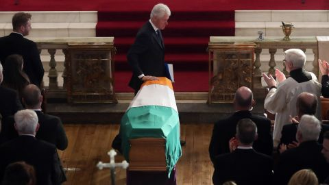 Former US President Bill Clinton touches the coffin Thursday of Martin McGuinness, the Northern Ireland politician and one-time IRA commander
