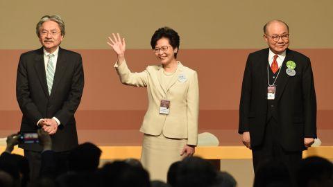 Hong Kong's next chief executive Carrie Lam (center) stands with rivals John Tsang (left) and Woo Kwok-hing.