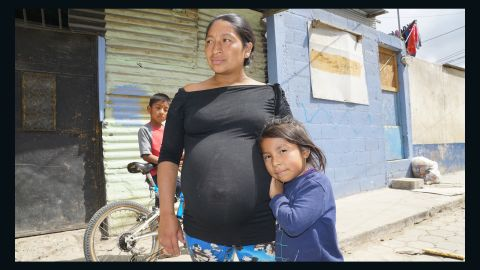 Angelina, a pregnant mother of three, and her youngest daughter, Charon, outside their home in Guatemala City.