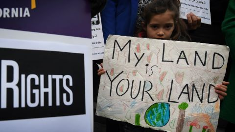 """Maya Casillas, 7, joins migrant rights group during a vigil to protest against President Donald Trump's new crackdown on """"sanctuary cities"""", outside the City Hall in Los Angeles on January 25, 2017."""